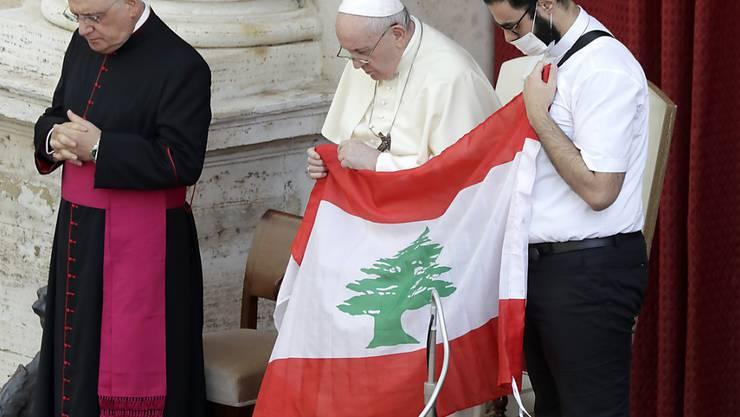 Papst Franziskus (M) hält bei seiner ersten Generalaudienz mit Gläubigen seit Ausbruch der Corona-Pandemie in Gedenken an die Opfer der Explosion die Flagge des Libanon. Foto: Andrew Medichini/AP/dpa