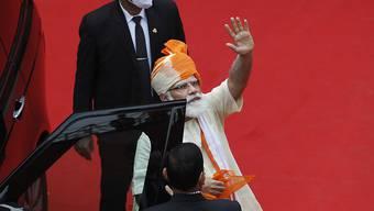 Narendra Modi (r), Premierminister von Indien, winkt, nachdem er am Unabhängigkeitstag vor den Stadtmauern des historischen Red Fort Monuments eine Rede gehalten hat. Foto: Manish Swarup/AP/dpa