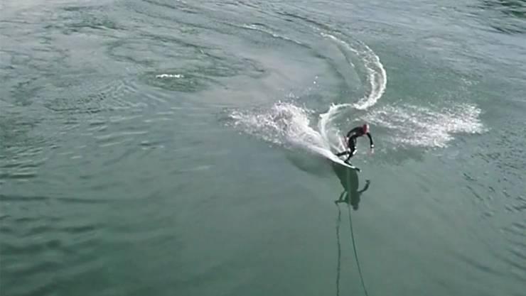 Mit einem elastischen Seil an der Holzbrücke surft Sebastian Dessecker auf dem Rhein.
