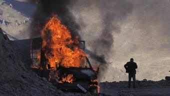 dpatopbilder - Ein Mann steht in der Nähe seines brennenden Autos, das beim Aufstieg entlang der Straße zu einem Bergpass nahe der Grenze zwischen Berg-Karabach und Armenien in Brand geraten ist. Foto: ---/AP/dpa