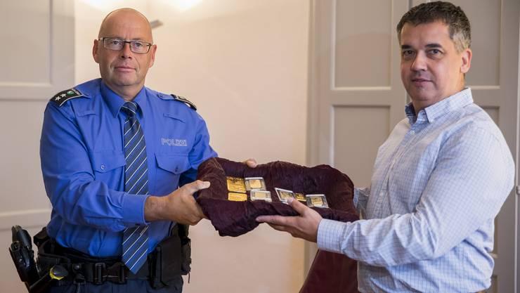<p>Polizeichef Zurzibiet Rene Lippuner überreicht Gemeindeammann von Klingnau Oliver Brun die im Jahre 2012 gefundenen Goldbarren.</p>