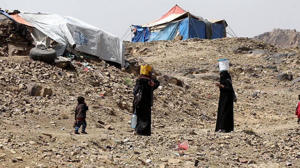 Frauen tragen Wasser in ihr behelfsmässiges Flüchtlingslager im Jemen.
