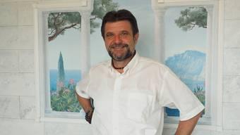 Alfons P. Kaufmann in seinem Büro vor einem südländischen Wandgemälde.