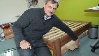 Thomas Etter «misst» in einem Haus in Schönenbuch die Strahlung von Wasseradern mit einer Wünschelrute. Unter dem Rost sind die Holzlatten zu erkennen, welche das Bett abschirmen sollen.