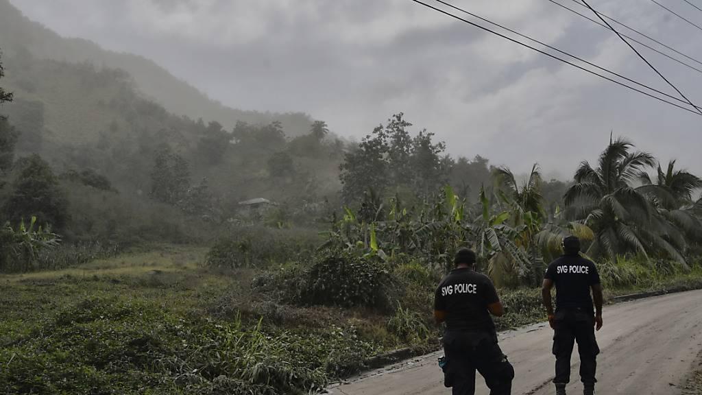 Polizisten patrouillieren nach dem Ausbruch des Vulkans La Soufrière auf einer aschebedeckten Straße, um Menschen davon abzuhalten, sich dem aktiven Vulkan zu nähern. Foto: Orvil Samuel/AP/dpa