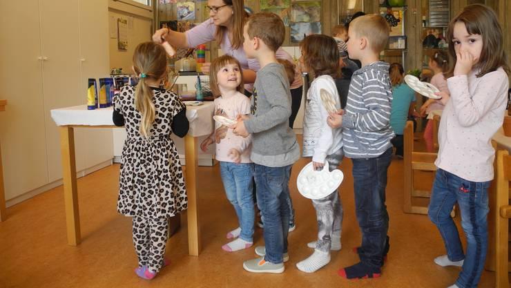 Welche Farbe darf es sein? Die Kinder stehen mit ihren Paletten an, um Malfarben für ihre Töpfe zu erhalten.