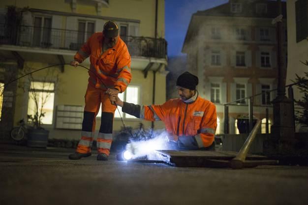 Markus Meier und Thomas Seger (im Schacht) bürsten die Quellleitungen mit sogenannten Ruten durch: lange Kabel mit einem Bürstenkopf.