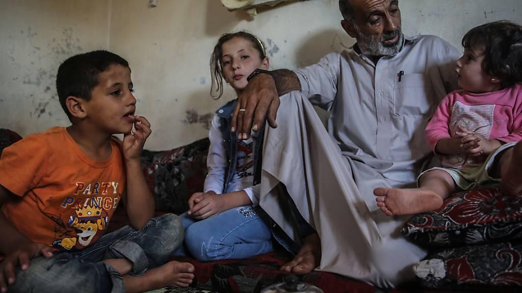 Der Lebensmittelverkäufer Khaled Amash spricht mit seinen Kindern in seinem neuen Haus. Das alte Haus von Amash wurde nach einem Bombenangriff durch regimetreue Kräfte zerstört. Foto: Anas Alkharboutli/dpa