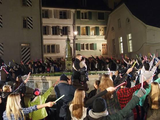 Alle Protagonisten des Flashmobs umringen das Liebespaar und schwenken ihre Leuchtstäbe
