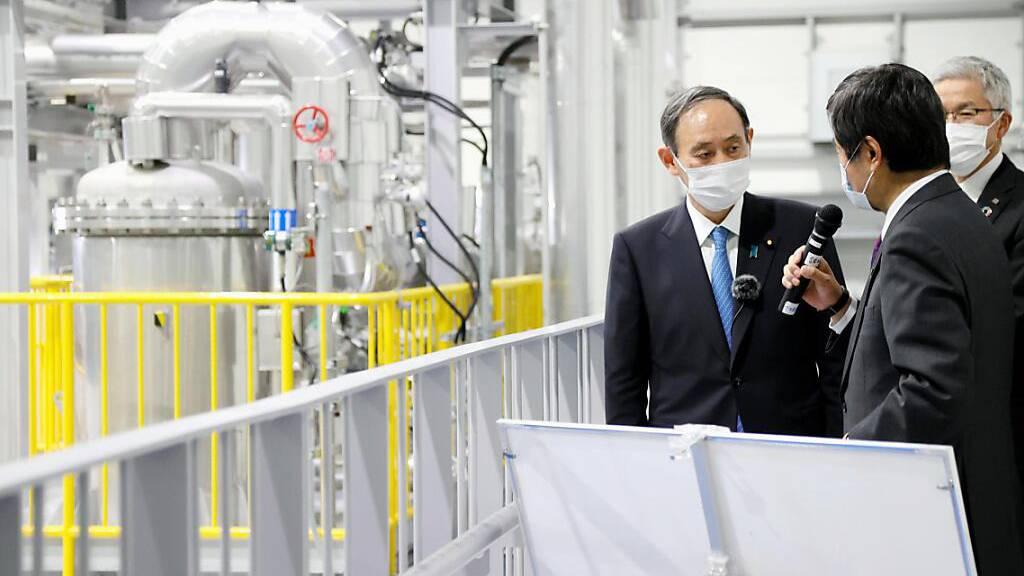 Yoshihide Suga (l), Ministerpräsident von Japan, besucht ein Roboterentwicklungszentrum in der Nähe des havarierten Atomkraftwerks Fukushima Daiichi. Am 11. März 2021 findet der 10. Jahrestag der Tsunami-Katastrophe in Fukushima statt. Foto: ---/Kyodo/dpa
