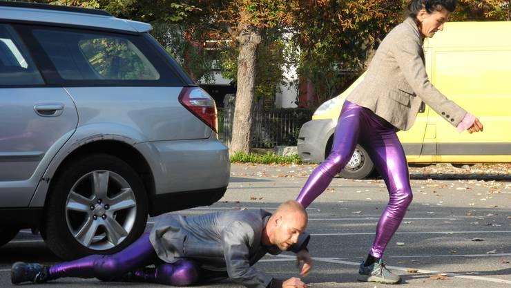 Ernteten verwunderte Blicke Zwei Mitglieder des Ensembles tanzen über einen Parkplatz