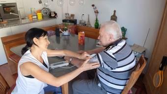 Pflegerin Ramona Walser misst dem pensionierten Bauer Werner Spörri * nach der Körperpflege den Blutdruck.