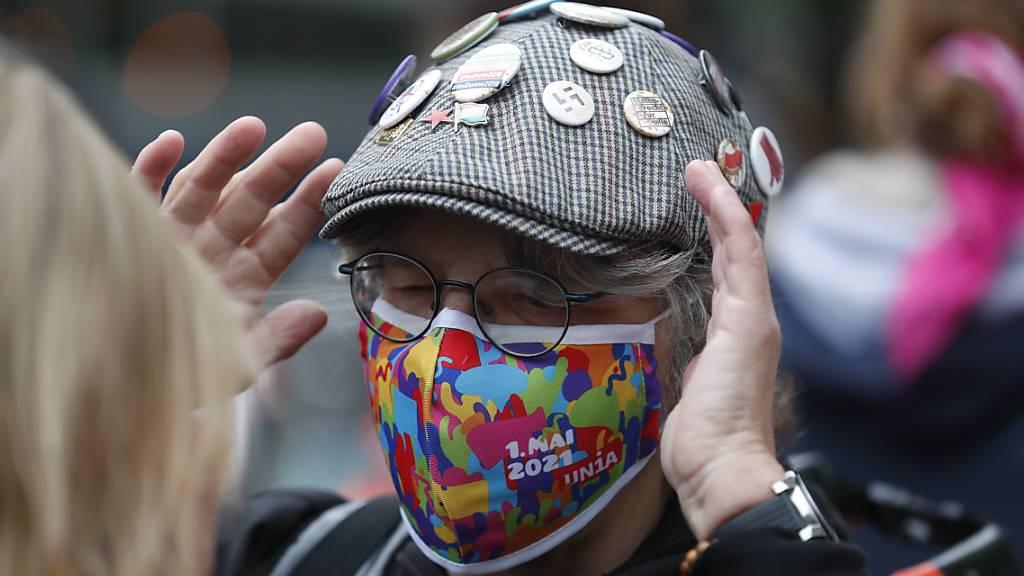 An einer Kundgebung zum Tag der Arbeit demonstriert ein Mann mit einer farbenprächtigen Corona-Gesichtsmaske der Gewerkschaft Unia  im Zentrum von Zürich.