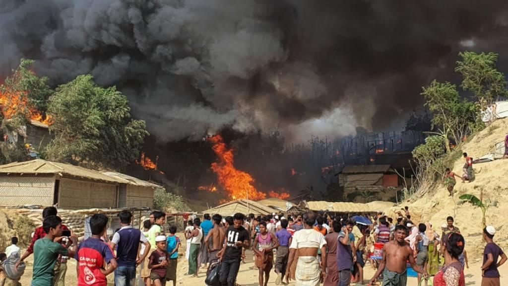 Zahlreiche Menschen betrachten den Rauch, der über dem in Flammen stehenden Lager in Bangladesch aufsteigt. Foto: Shafiqur Rahman/AP/dpa