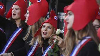 Eher konservative Frauen protestieren in Paris. Sie tragen die sogenannte Freiheitsmütze (phrygische Mütze) der Jakobiner der Französischen Revolution, die in der politischen Ikonografie Frankreichs und ganz Europas zum Symbol demokratischer und republikanischer Gesinnung wurde.