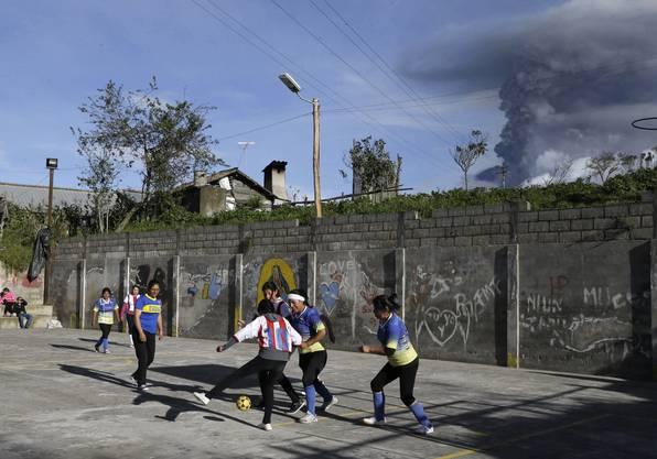 Kinder spielen auf der Strasse - im Hintergrund spuckt der Vulkan Tungurahua