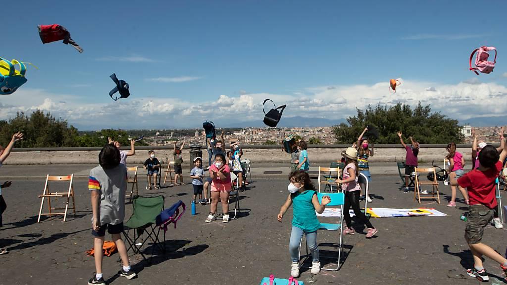 ARCHIV - Schulkinder werfen im Rahmen des Flashmobs «Apriti Scuola!» (Öffnet die Schule) auf dem Hügel Gianicolo ihre Schulranzen in die Luft. Foto: Alessandra Tarantino/AP/dpa
