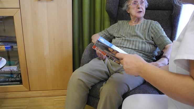Eine Sozialhilfebezügerin liest im Rahmen von Travo einer Bewohnerin des Altersheims Ruggacker vor.