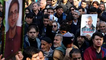 Teilnehmer an einer Beerdigung von sechs Abschuss-Opfern halten das Bild des ETH-Doktoranden Amir Ashrafi (links) in die Luft. Gleich daneben wird dem hohen Militär Qasem Soleimani gedacht. (Bild: Abbas Poustin Douz/Mehr Newsagency)