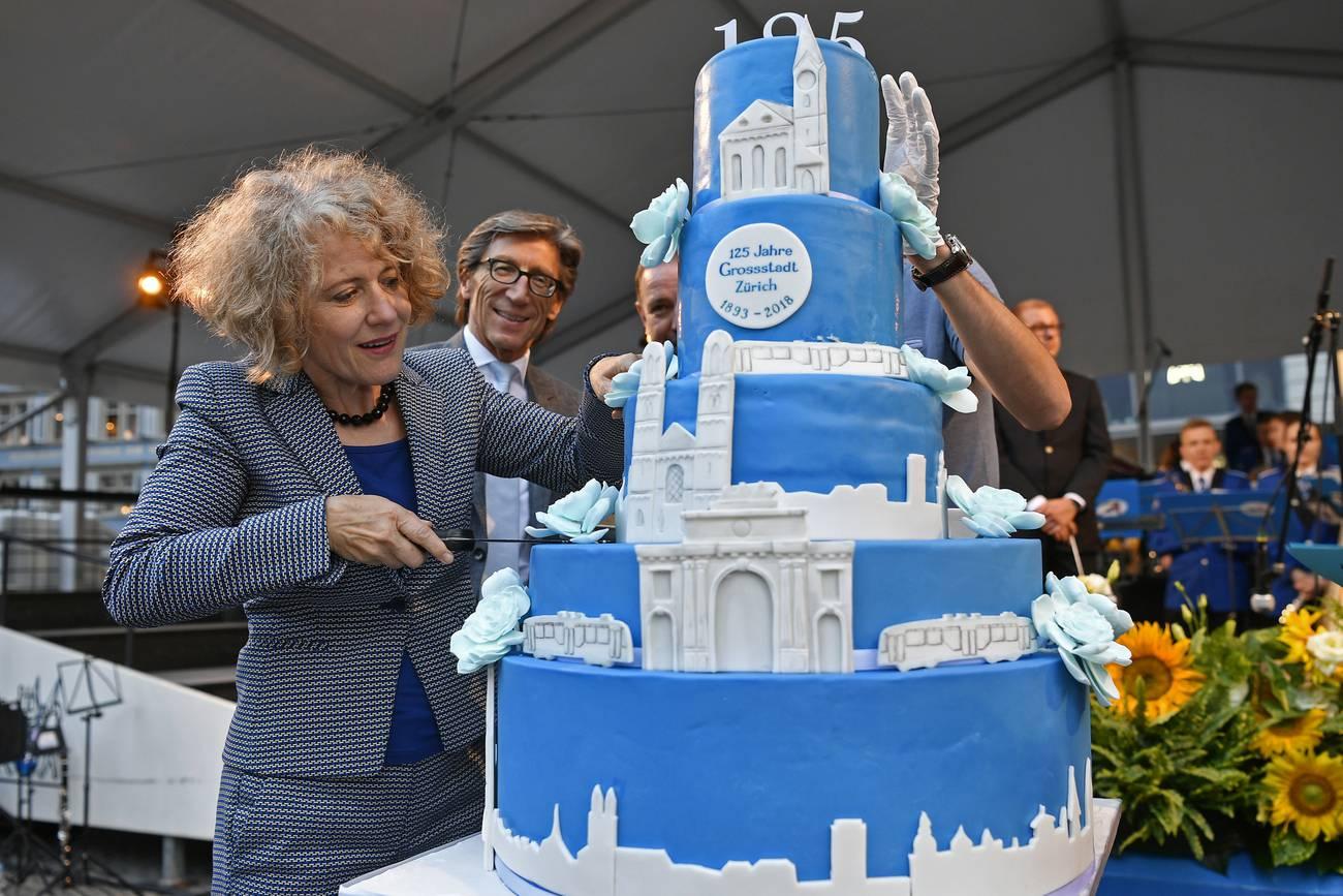 Corine Mauch schneidet die Torte beim Platzfest auf dem Münsterhof an anlässlich von «125 Jahre Grossstadt Zürich» im Juli 2018. (© Keystone)