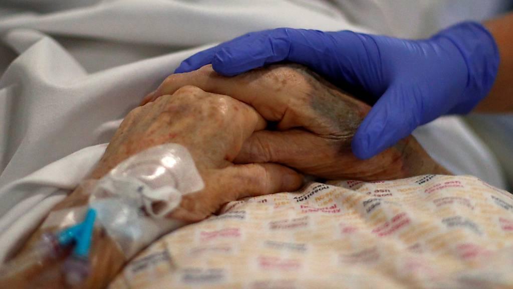 ARCHIV - Ein Radiologe hält die Hand eines Patienten im Royal Blackburn Lehrkrankenhaus, bevor er geröntgt wird. Foto: Hannah Mckay/PA Wire/dpa
