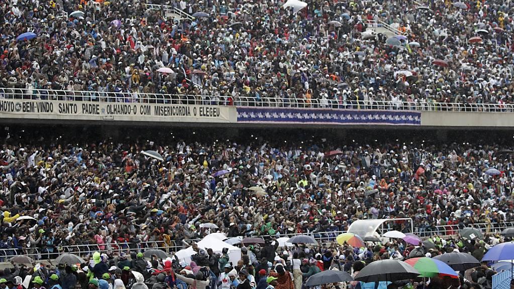Papst Franziskus fährt mit dem Papst-Mobil ins Zimpeto Stadion. Er wird von zehntausenden Gläubigen empfangen, die Regen und Wind trotzen, um dem Oberhaupt der Katholischen Kirche zu lauschen.