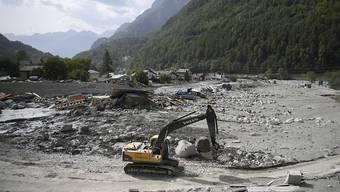 Ein Bagger schaufelt Material aus dem Auffangbecken in Bondo. (Archiv)