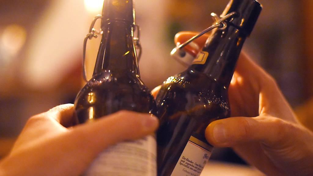 ARCHIV - ILLUSTRATION - Zwei Personen stoßen mit Bier an. Foto: Angelika Warmuth/dpa