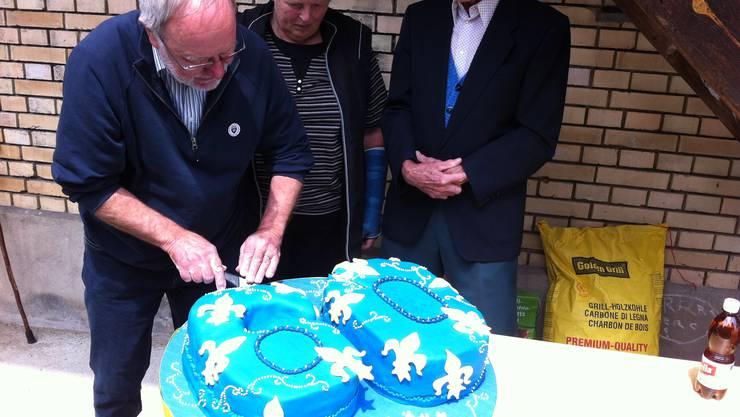 Präsident Hansruedi Elmer schneidet die Geburtstagstorte an.
