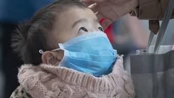 Zusammen mit ihrer Mutter wartet die kleine Tramy auf dem Flughafen Frankfurt am Check-In-Schalter einer vietnamesischen Fluggesellschaft. Dabei trägt sie eine Mundschutzmaske. Aus Vorsicht vor dem Corona-Virus.