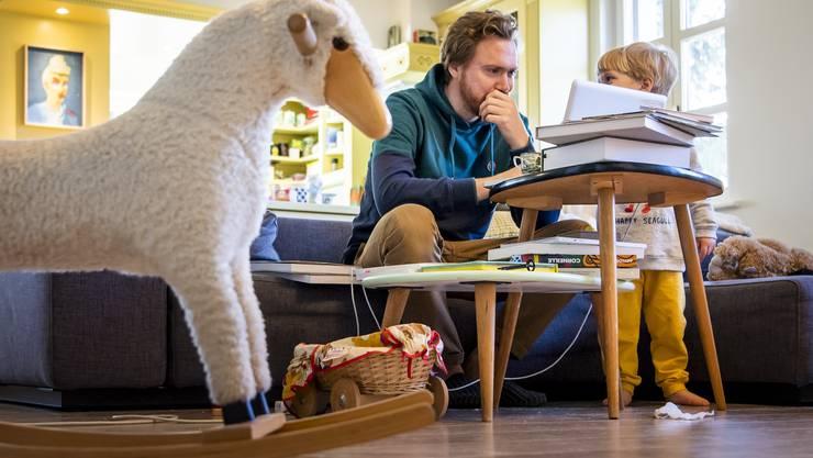 Arbeiten und gleichzeitig das Kind hüten: Ein Vater aus dem Kanton Waadt im Home-Office.