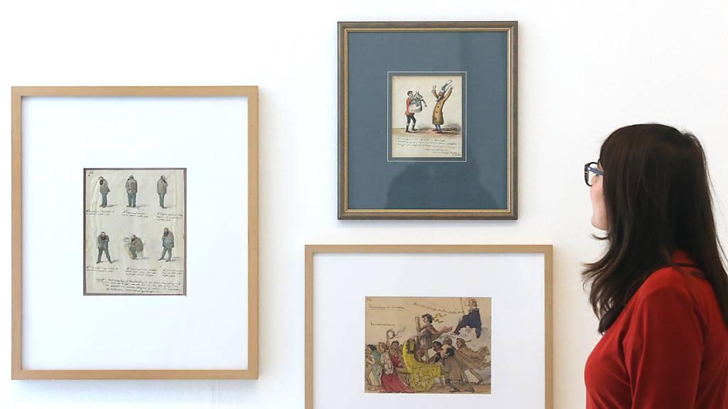 Eine Zeichenserie von Graf von Pocci (1850) schaut sich in der Ausstellung «Unveröffentlicht - Die Comicszene packt aus» eine Fachbesucherin an. Geplant ist ein umfassender Überblick zu bisher ungesehenen Werken der deutschsprachigen Comicszene. Gezeigt werden mehr als 300 Zeichnungen von mehr als 50 Comiczeichnerinnen und Zeichnern in der Ludwiggalerie Schloss Oberhausen. Foto: Roland Weihrauch/dpa - ACHTUNG: Nur zur redaktionellen Verwendung im Zusammenhang mit der aktuellen Berichterstattung über die Ausstellung und nur im vollen Format zu verwenden.