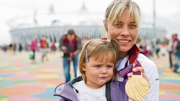 Edith Wolf-Hunkeler posiert mit ihrer Tochter Elin und der Goldmedaille über 5000 Meter.