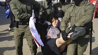 Polizisten tragen am Rande einer Demonstration in Minsk eine Frau weg. Foto: Uncredited/TUT.by/dpa