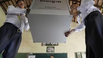 Mitglieder des kambodschanischen Wahlkomitees bereiten in einem Lokal eine Urne für die Stimmabgabe vor.