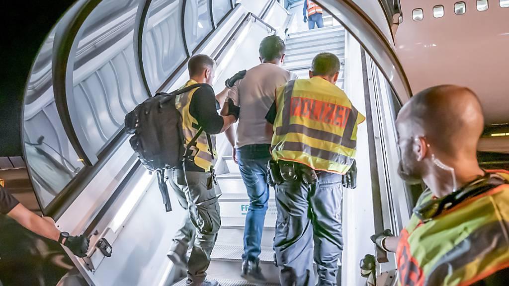 ARCHIV - Polizeibeamte begleiten einen Afghanen auf dem Flughafen Leipzig-Halle in ein Charterflugzeug. Die EU-Botschafter in Afghanistan raten angesichts des schnellen Vormarsches der Taliban von Abschiebungen in das Krisenland vorerst ab, heißt es in einem internen Bericht der EU-Missionschefs in Kabul. Foto: Michael Kappeler/dpa