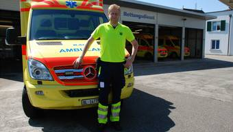Rettungssanitäter Kevin Pfister vor einem Fahrzeuge der Käch Falck AG. thb