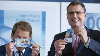 Die Schweizerische Bankiervereinigung kritisiert die Nationalbank für die Negativzinspolitik. Im Bild: SNB-Direktor Thomas Jordan (rechts) bei der Präsentation der Hunderternote.