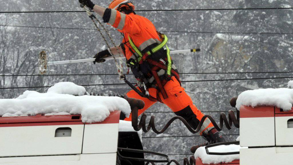 Ein Bahnarbeiter kontrolliert mit einem Schneebesen in der Hand eine Fahrleitung. Schneebedingte Fahrleitungsstörungen sind Standard, wenn es stark schneit - ein Eisblock, der wie im Val-de-Travers einen Zug stoppt, nicht. (Archiv)