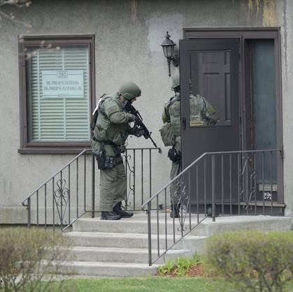 Polizisten gehen von Haus zu Haus
