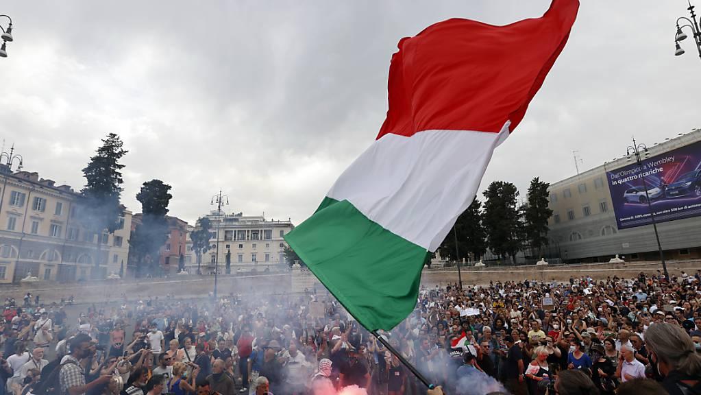ARCHIV - Vor dem Treffen der G20-Gesundheitsminister in Rom: Demonstranten zünden bei einer Demonstration gegen den geplanten «grünen Pass», eine Maßnahme zur Eindämmung des Corona-Virus, einen Bengalo. Laut Italiens Ressortchef Roberto Speranza soll die Zusammenarbeit beim Impfen verstärkt werden. Foto: Riccardo De Luca/AP/dpa