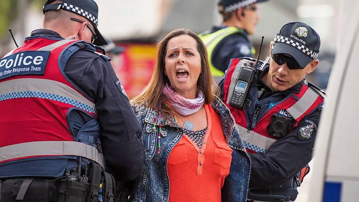Strassenkreuzung blockiert: In der australischen Metropole Melbourne wird eine militante Tierschützerin von der Polizei weggeführt.