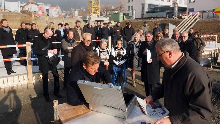 Der Koffer für den Grundstein wird mit Dokumenten gefüllt. Daran beteiligen sich Markus Spiess, Fiba Real Estate, Gemeindepräsident Markus Flury (rechts), Peter Schmid, Verkaufsleiter Coop-Verkaufsregion Bern, Tom Jungreitmair, Ducksch-Anliker Architekten AG (links).
