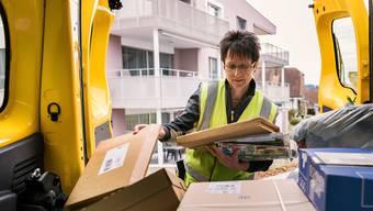 Eine Post-Mitarbeiterin liefert Päckli aus (Bild: Keystone/Christian Beutler (Mauensee, 21.3. 2017)).