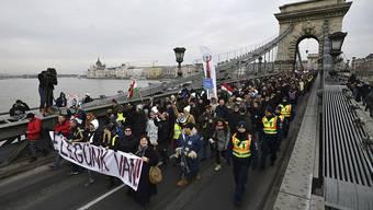 """Demonstrierende in Budapest tragen ein Transparent mit der Aufschrift: """"Wir haben es satt"""". Sie protestieren gegen ein neue Überstundengesetz und die Korruption im Umfeld der Orban-Familie."""