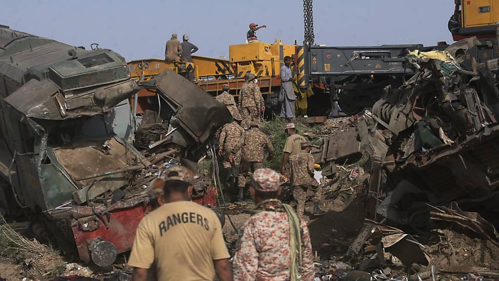Soldaten kommen an, um die Strecke an der Stelle einer Zugkollision im Bezirk Ghotki im Süden Pakistans zu räumen.