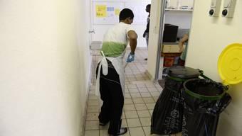 Ein Mann wischt den nimmt den Boden nass auf, aufgenommen im Asylzentrum Juch AOZ.