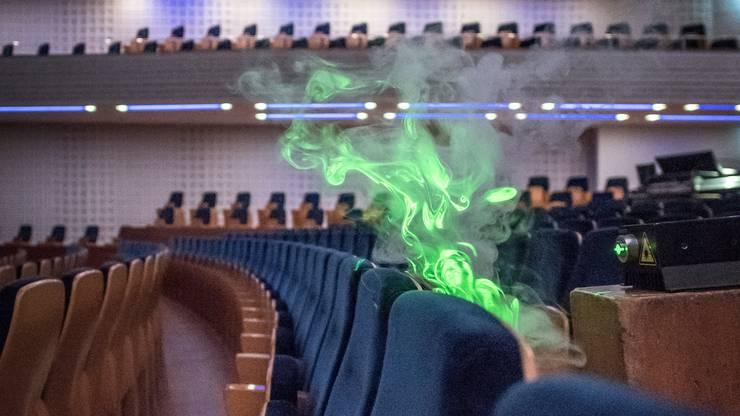 Wenig Ausbreitung: Der Nebel steigt durch die Lüftungsschlitze entlang eines Sitzes über dem Kopf des Zuhörers im KKL hoch.