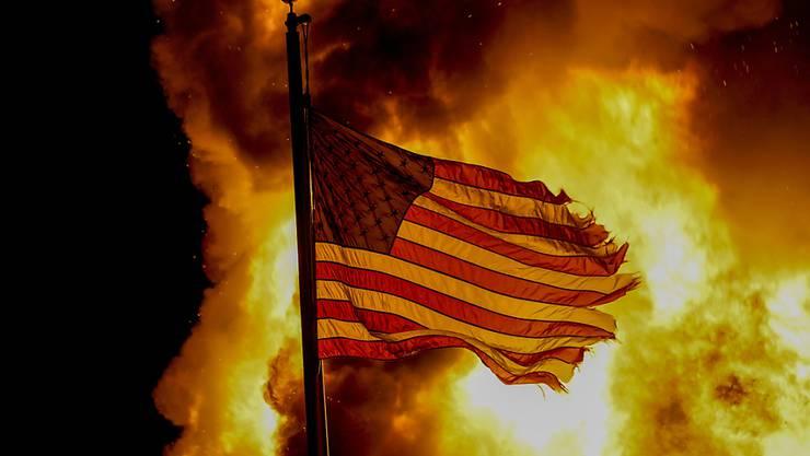 Eine ausgefranste US-Flagge weht vor den Flammen eines Feuers bei einem Protest nach den Schüssen auf Jacob Blake. Foto: Morry Gash/AP/dpa