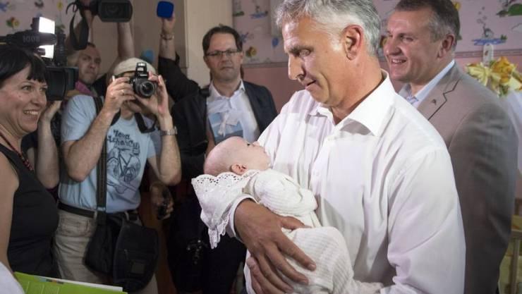 """Didier Burkhalter - damals noch Aussenminister - vergangenen Juni mit einem ukrainischen Findelkind im Arm. Kindern aus aller Welt hat er sein Buch """"Enfance de terre"""" gewidmet, das demnächst erscheint. (Archivbild)"""